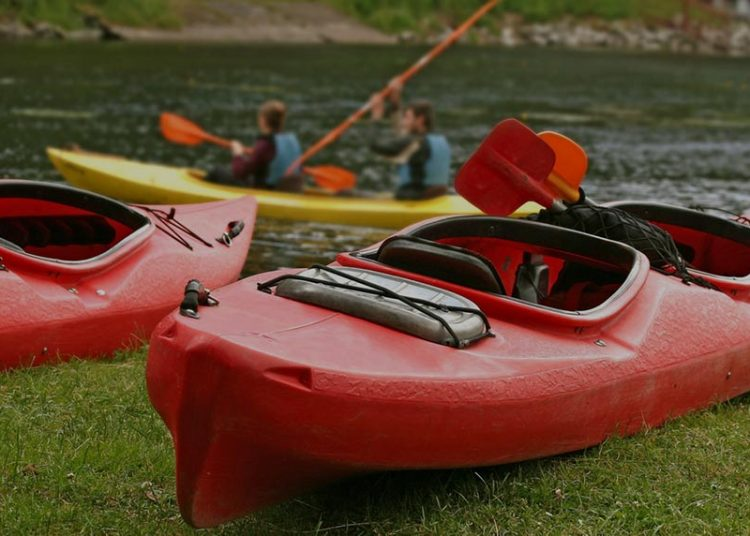 two red kayaks on the bank of a lake
