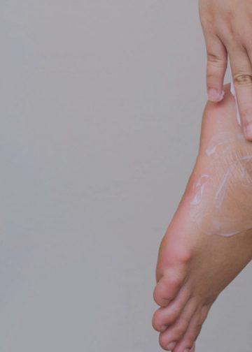 lady rubbing footcream into her skin