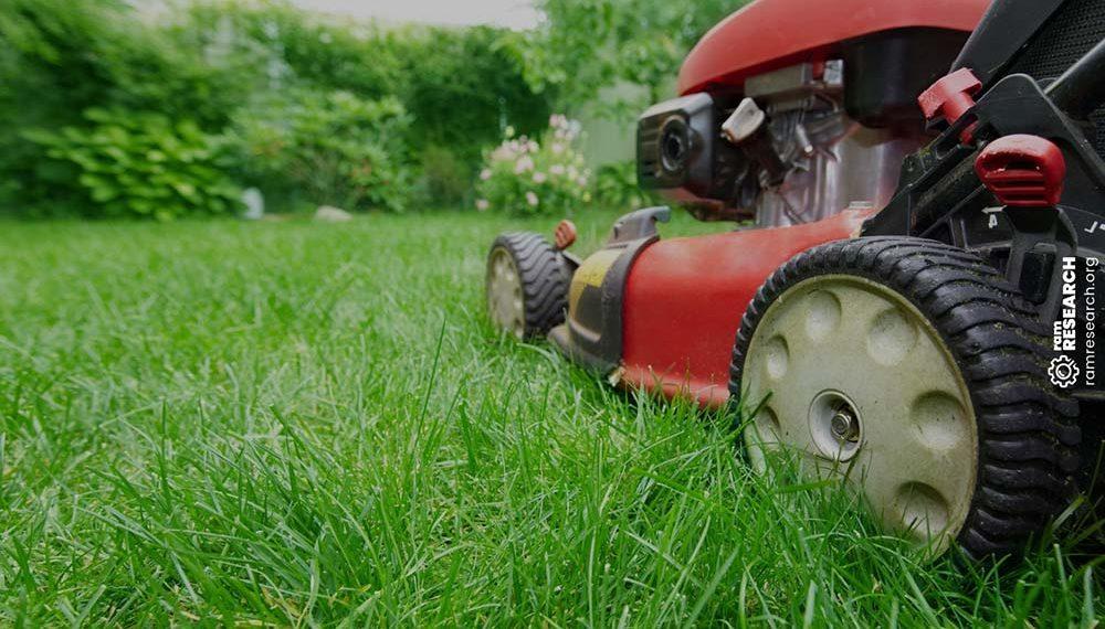red mower cutting green lush grass
