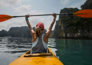 woman on a kayak holding a paddle above her head