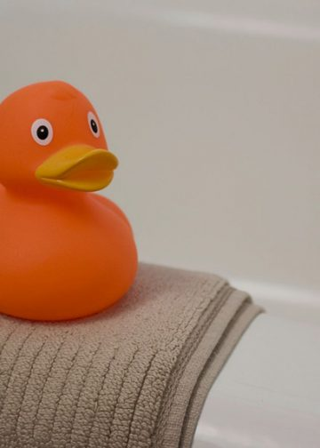 orange rubber ducky on a brown bath mat