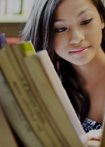 Asian lady looking through books on a shelf