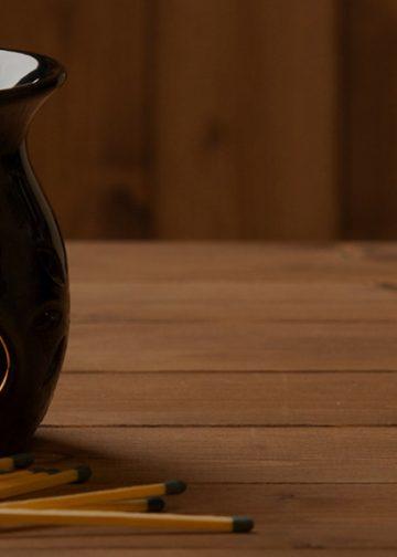 black oil burner with candle burning inside