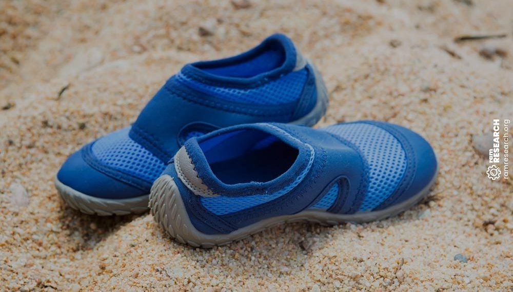 toddlers blue shoes in the sand at the beach