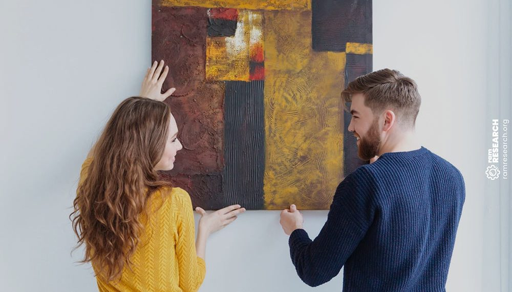 couple hanging and adjusting painting on the wall