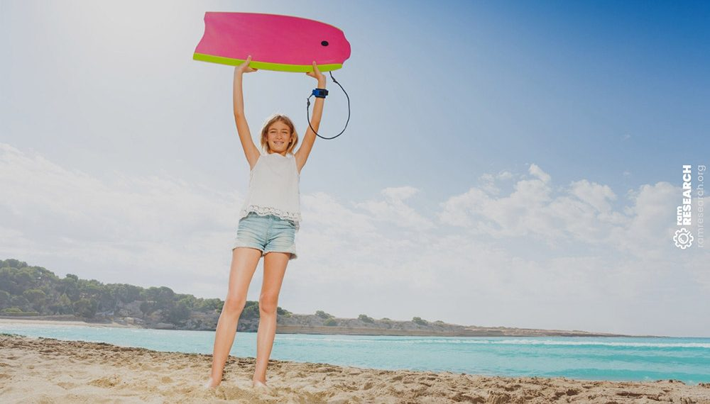 young girl holding up a pink bodyboard