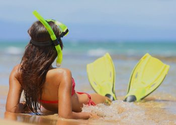 woman on the beach with snorkel fins on