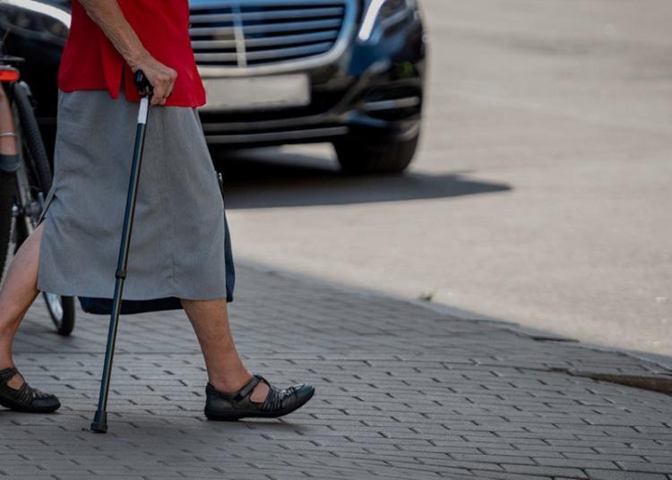 elderly woman crossing the footpath