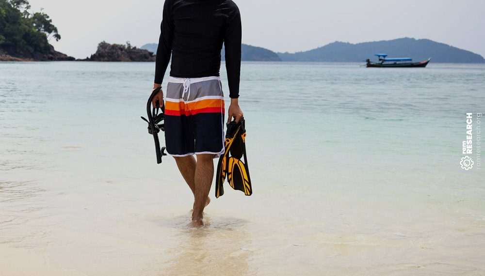 man carrying snorkel gear out of the ocean