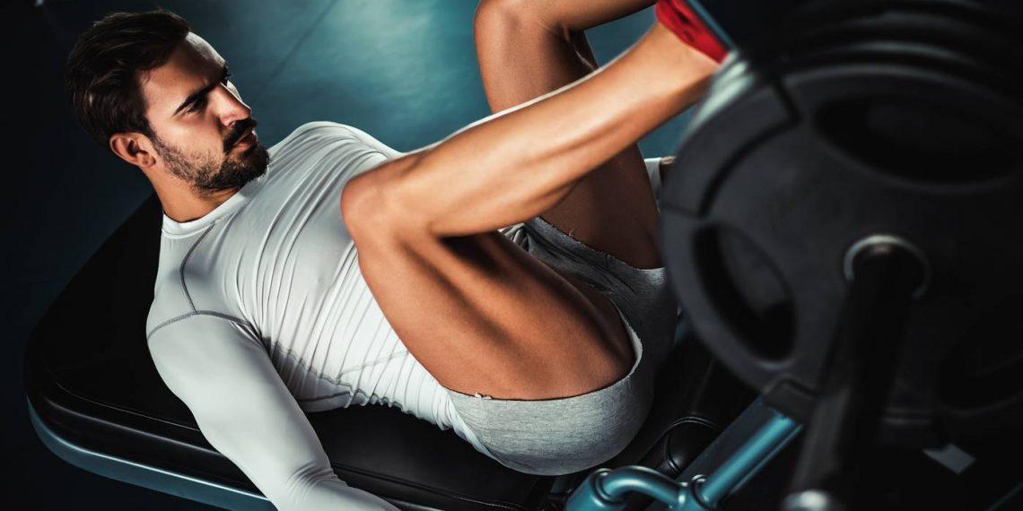 man training legs on leg press machine in the gym