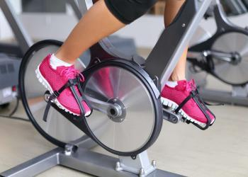 Woman with pink rubber shoes excising on a spin bike