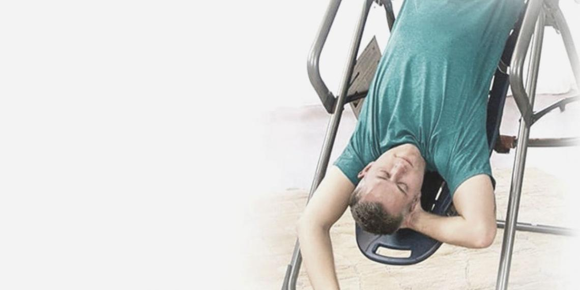 man inverted on an inversion table