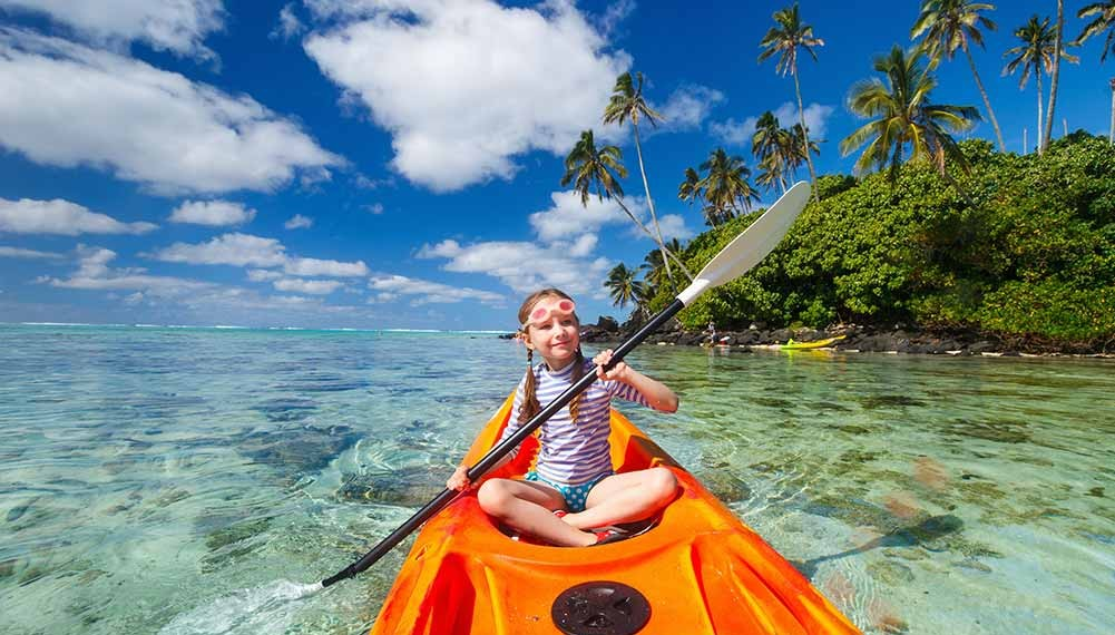 young girl on a kayak paddling over reef, palm trees in the background and a few clouds scattered across the blue sky