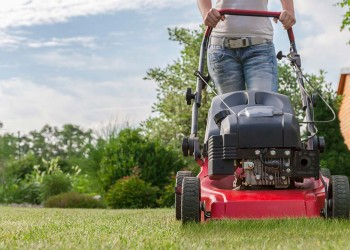 a person mowing the lawn with a brand new red lawnmower