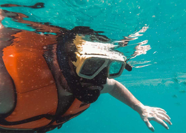 man snorkeling with a vest on