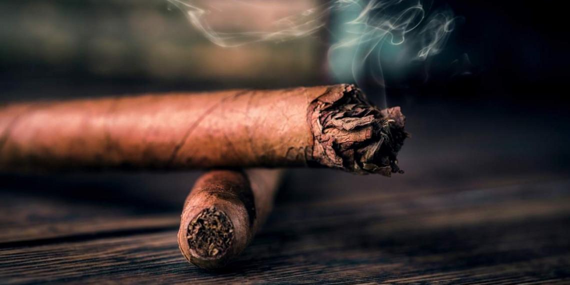 A lit cigar ontop of another cigar