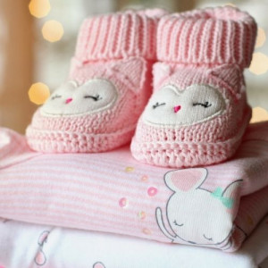 pink baby shoes on top of folded baby clothes