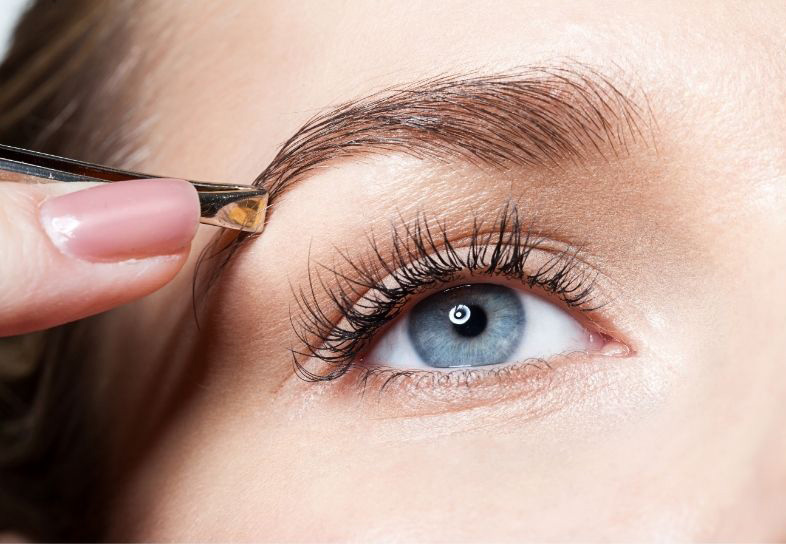woman using tweezers on her eyebrows